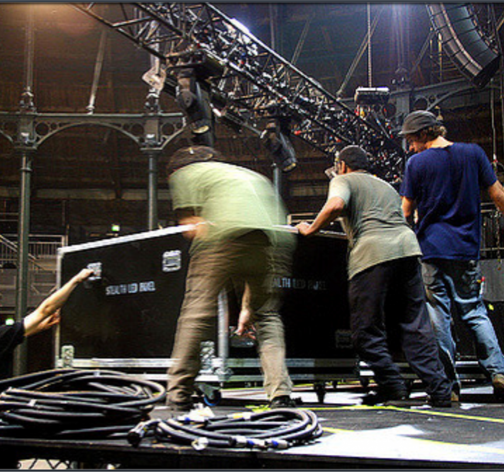 Roadies moving a box on stage